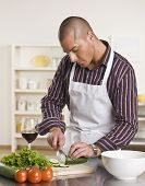 Attractive male cutting salad on the kitchen counter while drinking a glass of wine. vertical.