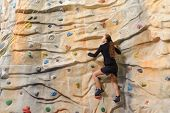 active young business woman on rock wall in sport center