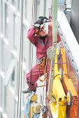 worker builder installing glass windows on facade of business building
