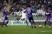 KAPOSVAR, HUNGARY - SEPTEMBER 14: Benjamin Balazs (in white) in action at a Hungarian National Championship soccer game- Kaposvar (white) vs Ujpest (purple) on September 14, 2012 in Kaposvar, Hungary.