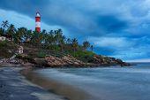 Gathering storm on beach and Kovalam (Vizhinjam) lighthouse on stormy sunset. Kerala, India