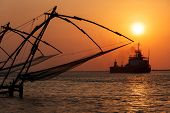 Kochi chinese fishnets on sunset and modern ship. Fort Kochin, Kochi, Kerala, India