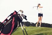 Girl golf player hitting ball on golf course with golf bag in foreground.