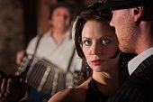 stock photo of debonair  - Beautiful tango dancer with partner and accordion musician - JPG