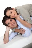 pic of futon  - Portrait of a happy couple lying on a futon - JPG