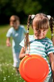pic of frisbee  - Happy boy and little girl playing frisbee on a meadow in a sunny day - JPG