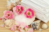 Spa treatment products with pink rose flower arrangement, sea salt, shells and white towels over bamboo background. Roses are Carefree Days variety.