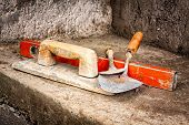 Trowels and other masonry tools on an unfinished concrete wall background