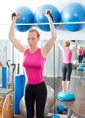 Bosu ball for fitness redhead woman in aerobics gym