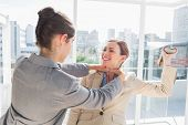 Businesswoman strangling her partner holding a shoe in bright office