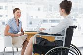 Businesswoman speaking with disabled colleague at desk in office