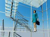 Business woman rises on the glass stairs.