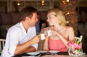 picture of hot coffee  - Couple Enjoying Cup Of Coffee In Restaurant - JPG