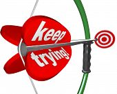 stock photo of perseverance  - The words Keep Trying on a bow and arrow aiming at a target to illustrate determination - JPG