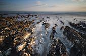 Longa exposição paisagem litoral rochoso ao pôr do sol