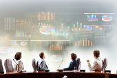 picture of four  - Image of businesspeople at presentation looking at virtual project - JPG