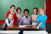 Portrait of happy African American female teacher and schoolchildren gesturing together at desk in classroom