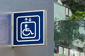 Blue Handicap Elevator Sign With Blurred Glass Background, Closeup