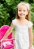 Cute Little Girl With Her Toy Carriage And Doll