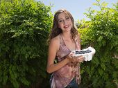 Young pretty woman holding bowl of blueberries outside