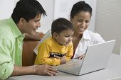 Happy young couple with son using laptop at desk
