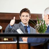 Happy concierge in hotel at reception showing his thumbs up