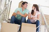 Casal sentado na escadaria com caixas na nova casa sorrindo