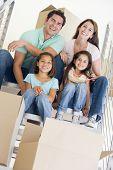Família sentado na escadaria com caixas na nova casa sorrindo