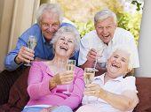 Twee paren op Patio drinken Champagne en glimlachen