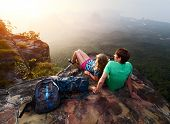 Young hikers relaxing on top of a mountain and enjoying sunrise