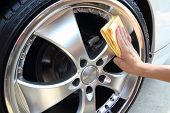 stock photo of orbital  - Hand with a microfiber wipe coated wheels car wash - JPG
