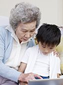 image of grandma  - grandma and grandson looking at tablet computer together - JPG