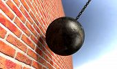pic of ball chain  - A regular metal wrecking ball attached to a chain hitting and breaking a face brick - JPG