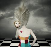 stock photo of surreal  - Sensual and fantasy back of a female model with long blond hair and corset who looks at her face in a mirror in a surreal background - JPG
