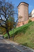 KRAKOW, POLAND - SEPTEMBER 15, 2013: People on the street under Senator tower of Wawel royal castle.