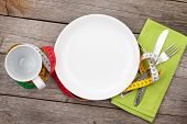 Plate with measure tape, cup, knife and fork. Diet food on wooden table