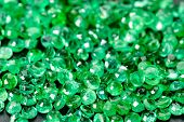 pic of emerald  - Large pile of green emeralds on black stone.