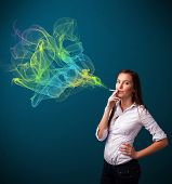 Pretty young lady smoking cigarette with colorful smoke