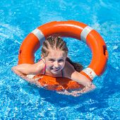 smiling cute  girl swims with a lifeline in the pool in  summer