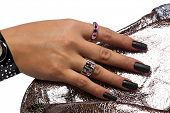 closeup of the woman�?�¢??s hand wearing luxury rings, black nail art manicure on silver sequin m