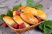 Fresh baked pasties with strawberries in a basket close-up
