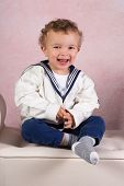 Cute little victorian toddler boy dressed in vintage sailor costume