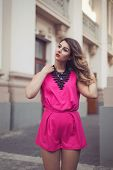 stock photo of jumpsuits  - Fashion glamorous and attractive woman dressed in a sexy sleeveless pink jumpsuit with a hand in her hair - JPG