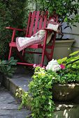 Colorful rocking chair in a cottage garden setting.