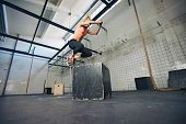 stock photo of jumping  - Low angle view of young female athlete box jumping at a crossfit gym - JPG