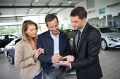 image of 35 to 40 year olds  - Couple signing car purchase order on digital tablet - JPG
