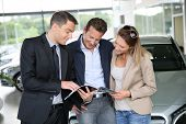 picture of 35 to 40 year olds  - Couple in car dealership looking at brochure with salesman - JPG