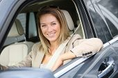 Cheerful woman at car window driving brand new vehicle