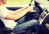 transportation and vehicle concept - man driving the car with manual gearbox