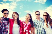 summer holidays and teenage concept - group of smiling teenagers hanging outside